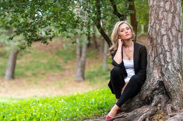 Elegante jonge blonde dame zit in het bos bij de boom en geniet van de stilte