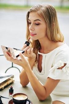Elegante jonge blonde vrouw compact poeder openen en rode vloeibare lippenstift toe te passen