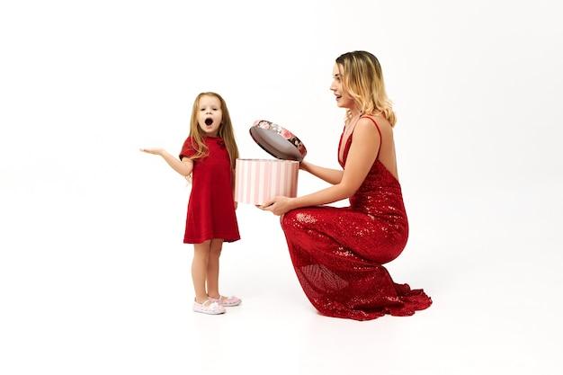 Elegante jonge blonde vrouw in rode jurk zittend op de vloer met doos, waardoor haar schattig meisje verjaardagscadeau
