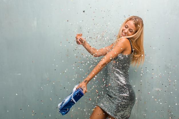 Elegante jonge blonde vrouw viert nieuw jaar met champagne, een geschenk en confetti.