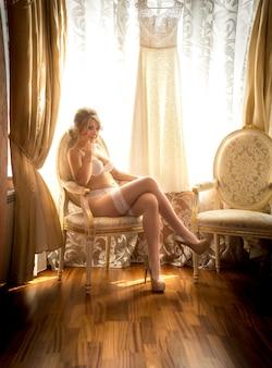 Elegante jonge bruid in witte lingerie die zich voordeed op stoel in hotelkamer