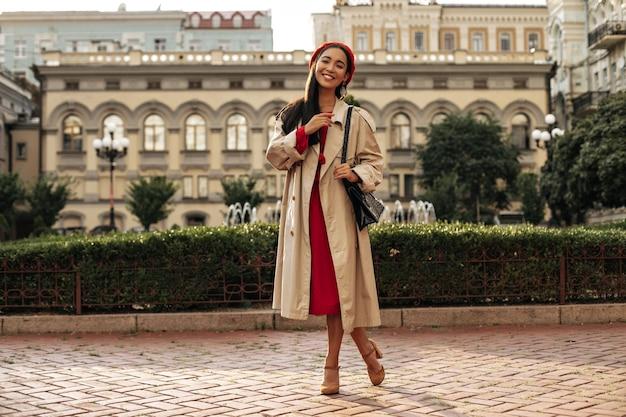 Elegante jonge brunette vrouw in stijlvolle beige trenchcoat, rode midi-jurk en baret glimlacht en poseert in een goed humeur buiten