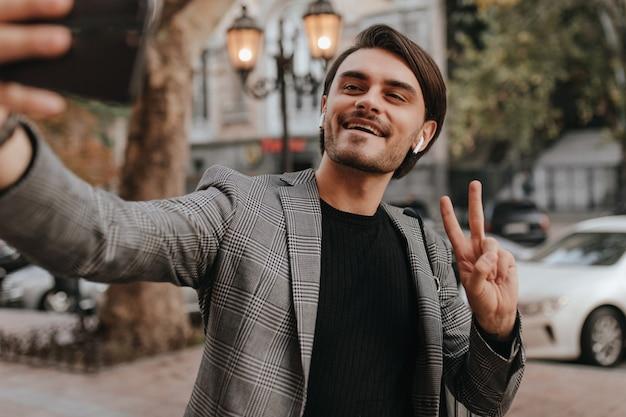 Elegante jonge donkerharige man in zwart shirt en trendy grijze blazer, telefoon vasthoudend en selfie makend tegen stadsmuur in de herfst