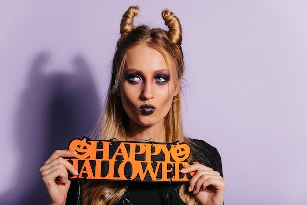 Elegante jonge heks die zich voordeed op paarse muur. blond meisje in vampier kostuum genieten van halloween.