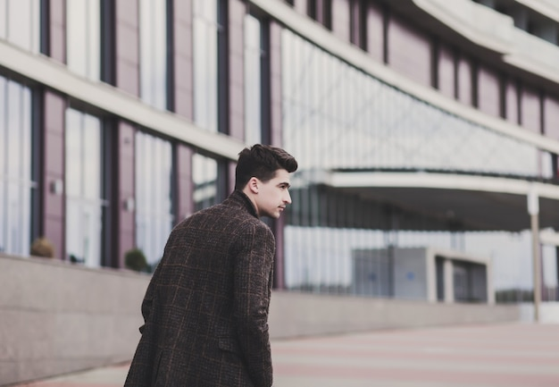 Elegante jonge knappe man in herfst jas. mode portret stijlvolle mannelijk model