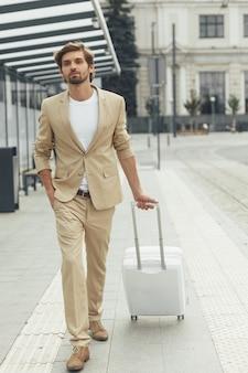 Elegante jonge man met trendy kapsel en baard gekleed in pak staan bij bushalte met koffer. reizend concept