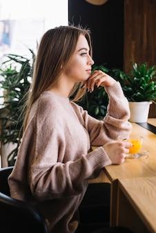 Elegante jonge nadenkende vrouw met kop van drank bij barteller in koffie