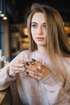 Elegante jonge nadenkende vrouw met kop van drank in koffie