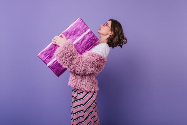 Elegante jonge vrouw die in bontjasje groot verjaardagsgeschenk houdt. kortharig meisje met roze geschenkdoos.