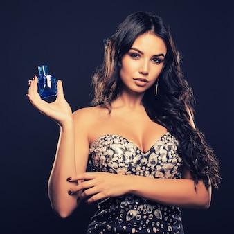Elegante jonge vrouw in een mooie jurk met parfum op donkere ruimte.