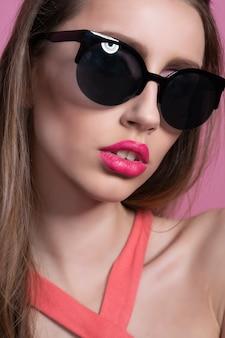 Elegante jonge vrouw in een vrij roze pak en zonnebril poseren op roze