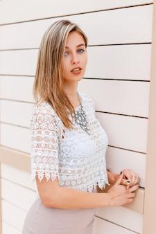 Elegante jonge vrouw in een witte kanten blouse met een stijlvolle beige rok met een luxe glanzende ketting poseren in de buurt van vintage houten muur buitenshuis
