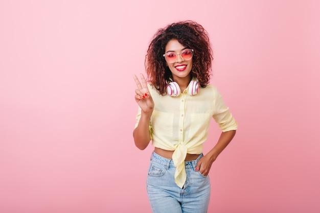 Elegante jonge vrouw in goed humeur poseren in nieuwe kleren. knap lief meisje met afrikaans kapsel.