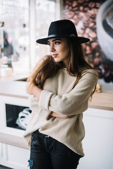 Elegante jonge vrouw in hoed met gekruiste handen