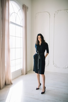 Elegante jonge vrouw in jurk in kamer