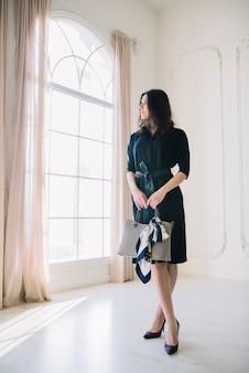 Elegante jonge vrouw in jurk met handtas in de kamer