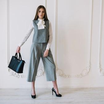 Elegante jonge vrouw in kostuum met handtas in de kamer