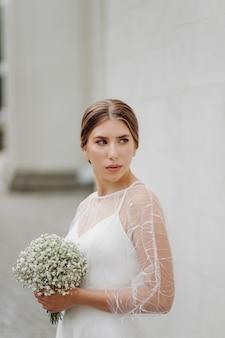 Elegante jonge vrouw in modieuze witte jurk staat in de buurt van muur