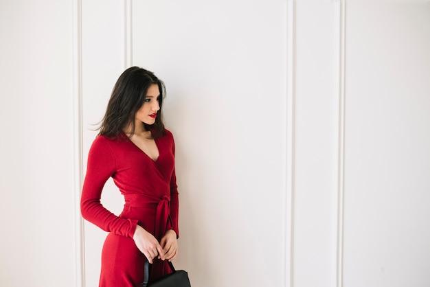 Elegante jonge vrouw in rode jurk met handtas in kamer