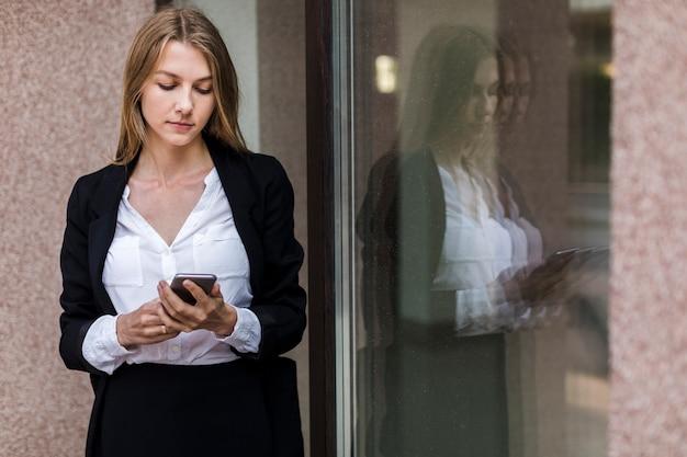 Elegante jonge vrouw met behulp van haar telefoon