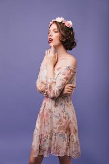 Elegante jonge vrouw met kort kapsel poseren met bloemen op haar hoofd. indoor portret van modieus meisje in een stijlvolle zomerjurk.