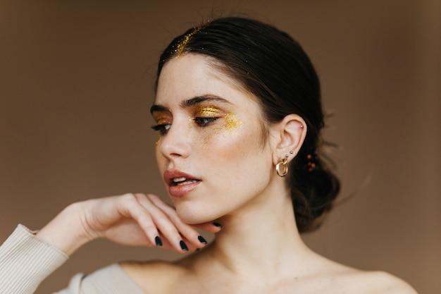 Elegante jonge vrouw met zwarte manicure die zich op bruine muur bevindt. sensuele brunette meisje poseren met open mond.