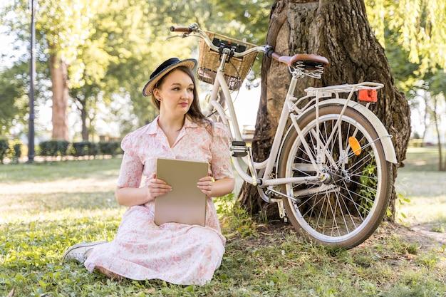 Elegante jonge vrouw poseren met fiets