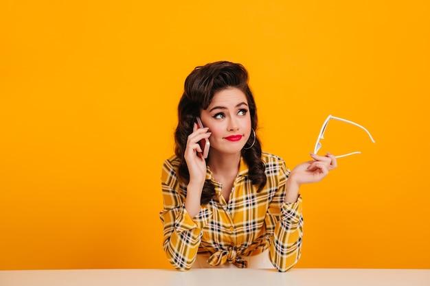 Elegante jonge vrouw praten over de telefoon op gele achtergrond. studio shot van prachtige pinup meisje met bril.
