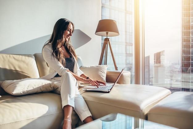 Elegante jonge vrouwelijke bedrijfsvrouw die laptop thuis met behulp van op een bank zitten.