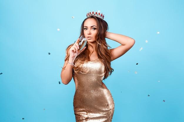 Elegante jongedame in gouden glitter jurk avond make-up met glas champagne en celebratin...