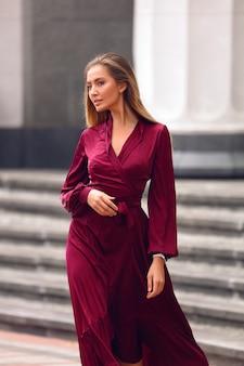 Elegante jongedame in lange bordeauxrode jurk met mouwen en tailleband. hand vasthouden onder de borsten. blond kapsel en natuurlijke naaktmake-up. lopend door de straat bij het gebouw.