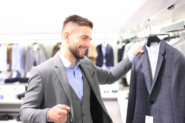 Elegante jongeman die een nieuw pak kiest in het winkelcentrum of de kledingwinkel.