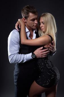 Elegante jongeman omarmt zachtjes zijn geliefde meisje in een zwarte jurk