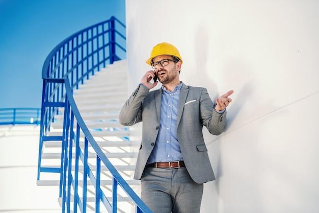 Elegante kaukasische welvarende zakenman in pak met helm op hoofd naar beneden de trap en praten met zakenpartner over olieprijs op de beurs.