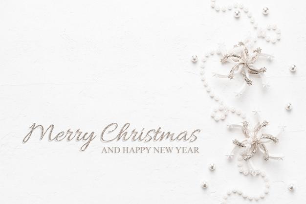 Elegante kerstkaart met parels en glitter decoraties op wit.