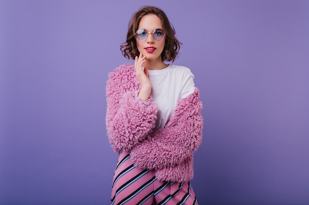 Elegante kortharige meisje in trendy zonnebril poseren met geïnteresseerde gezichtsuitdrukking. verbazingwekkende krullende dame in bontjas en gestreepte broek geïsoleerd op paarse muur.