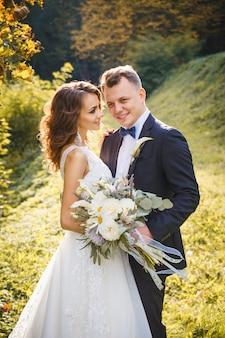 Elegante krullende bruid en stijlvolle bruidegom knuffelen in het park