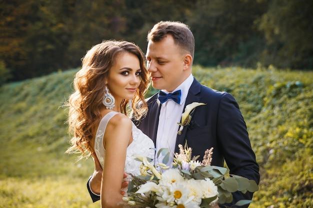 Elegante krullende bruid en stijlvolle bruidegom knuffelen op de groene weide