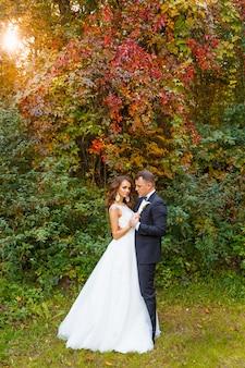 Elegante krullende bruid en stijlvolle bruidegom knuffelen op mooie groene achtergrond
