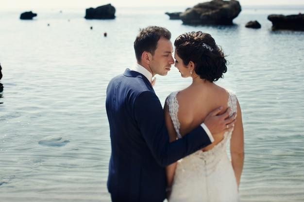Elegante lachende jonge bruid en bruidegom lopen op het strand