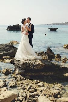 Elegante lachende jonge bruid en bruidegom poseren op de rotsen op het strand