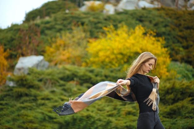 Elegante langharige blonde vrouw die een fladderende sjaal draagt, die zich voordeed in de botanische tuin. ruimte voor tekst