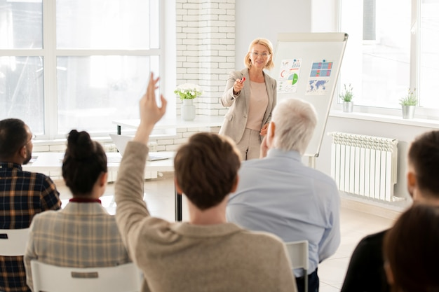 Elegante leraar wijzend op een van de studenten tijdens de les na het stellen van een vraag over de lezing