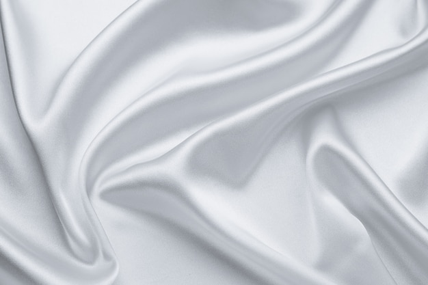 Elegante lichtgrijze stoffen achtergronden. metallic grijze kleur van glanzend textiel, zachte zilveren textuur. satijn vouwen, golvenpatroon. luxe mode. gladde glanzende kleding. zijden laken.