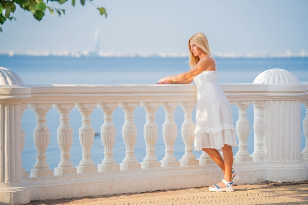 Elegante luxe vrouw in witte jurk genieten van het uitzicht op de zonsondergang op de promenade aan zee