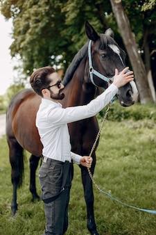 Elegante man die naast paard in een boerderij