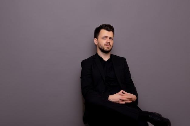 Elegante man in een klassiek zwart pak, zittend in de studio tegen een grijze achtergrond