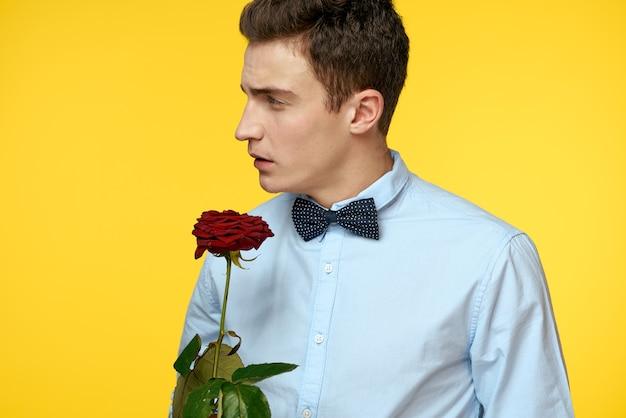 Elegante man in een pak met een rode roos in zijn handen op een gele achtergrond, bijgesneden weergave.