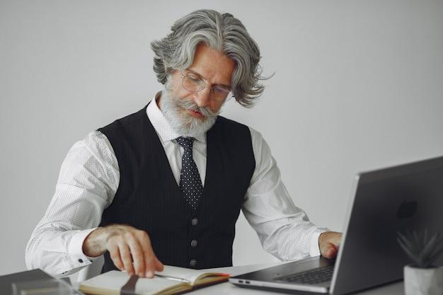 Elegante man in kantoor. zakenman in wit overhemd. man werkt met laptop.