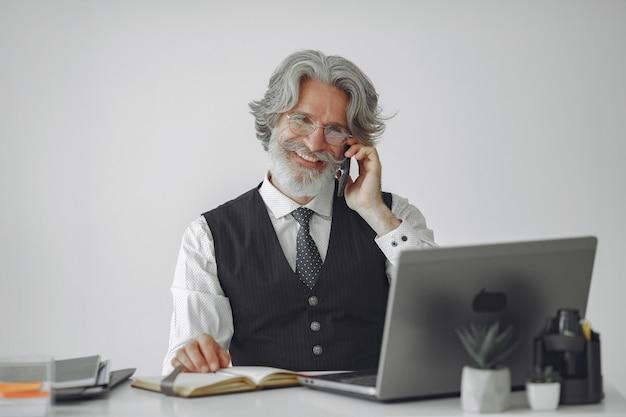 Elegante man in kantoor. zakenman in wit overhemd. man werkt met telefoon.